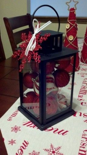 Fill a lantern with Christmas ornaments and tie a bow with ribbon towards the top of the lantern